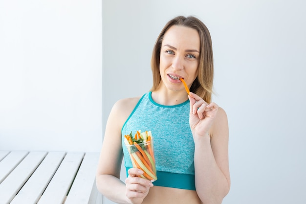 ダイエットのコンセプト-屋内で幸せな笑顔の野菜を食べる健康的なライフスタイルの女性。健康的な食べ物を食べる若い女性。
