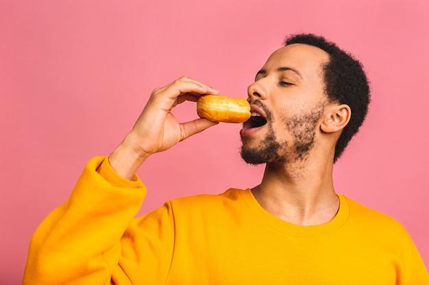 ダイエットのコンセプト。ピンクで隔離のドーナツを食べる空腹のひげを生やした男。