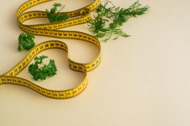 分離された測定テープと黄色の背景の食事療法の概念