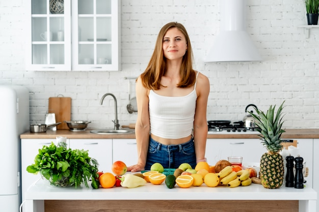 Diet concept. portrait of a healthy young woman with nice figure near the table with fruits and vegetables in the kitchen, concept of healthy food. vegan and vegeterian.