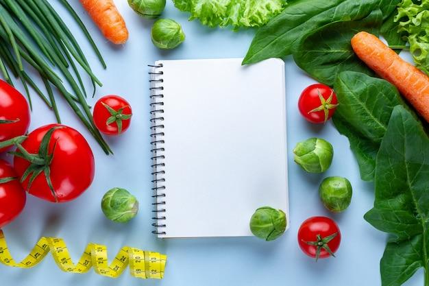 Концепция диеты. спелые овощи и пустой рецепт книги для приготовления свежих здоровых блюд. план диеты и дневник контроля