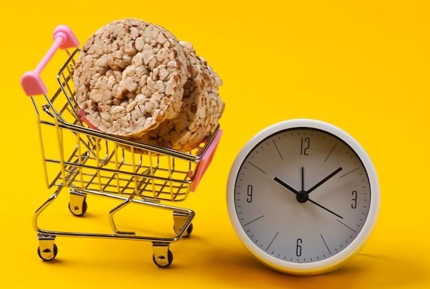ダイエットのコンセプト。全粒粉のクリスプブレッドと黄色の背景の時計とショッピングトロリー