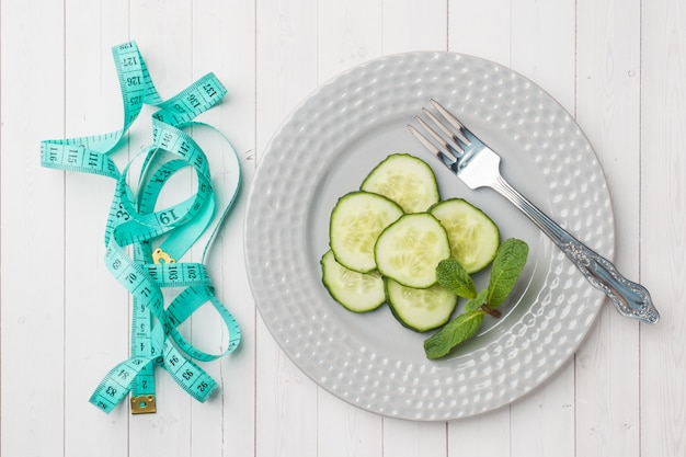 Diet concept. slides of fresh cucumber on a plate and tape centimeter on a white table.