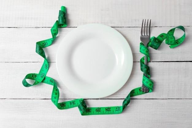 ダイエットコンセプト。痩身と重量損失の概念。フォークと巻尺で木製のテーブルの上の空のプレート