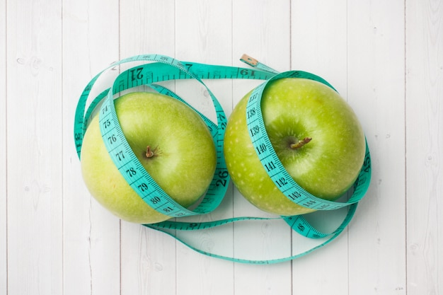 Diet concept. two green apples and a roulette wheel on a white table.