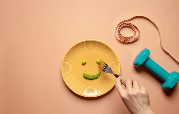 ダイエットコンセプト。フォークを使って皿の上の緑の大豆を食べる。ダンベルとソフトメジャーテープに囲まれています