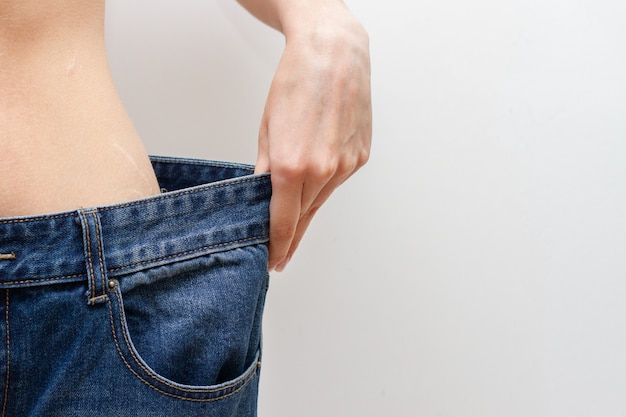 Diet concept and weight loss. woman in oversize jeans.