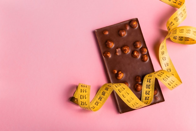 Diet concept with chocolate bar and measuring tape for weight loss on pink background.