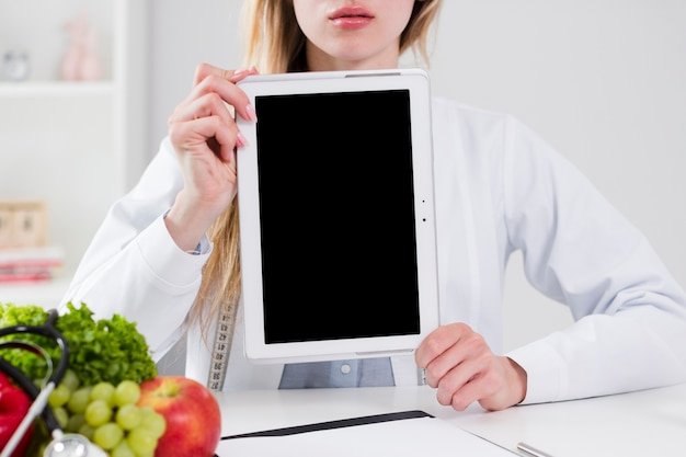 Diet concept with female scientist showing tablet template