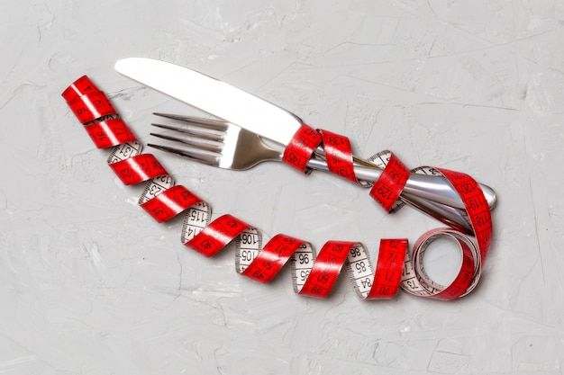 Diet concept with fork, knife and measuring tape