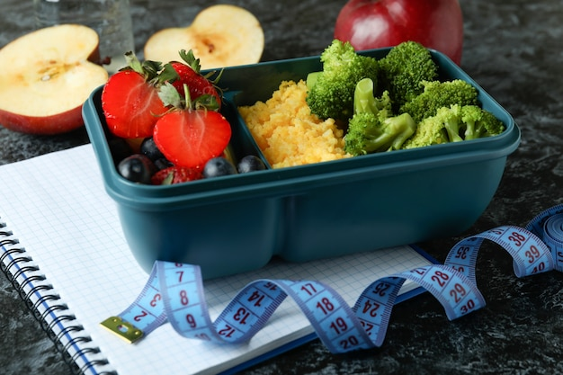Diet concept with lunch box on black smokey table