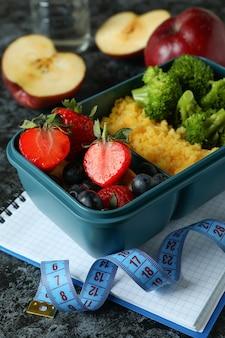 Концепция диеты с ланч-боксом на черном дымчатом столе