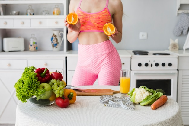 Diet concept with sporty woman in kitchen