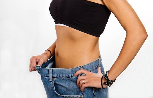 Концепция диеты: молодая женщина после диеты с большими джинсами