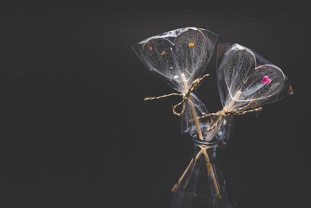 Diet curly lollipops. transparent and with bright elements. on a stick. on a black background.