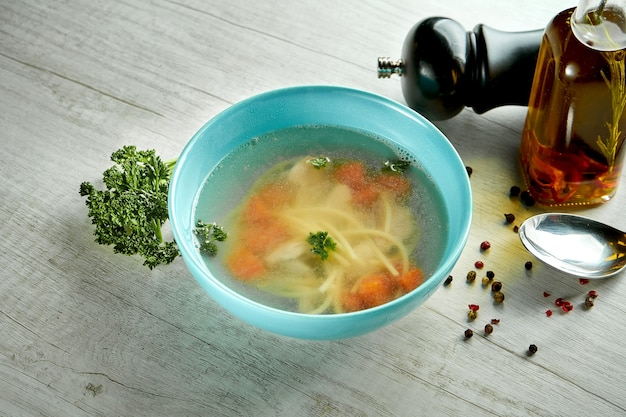 Diet and delicious chicken broth with vegetables, served in a blue bowl on a wooden table. healthy food.