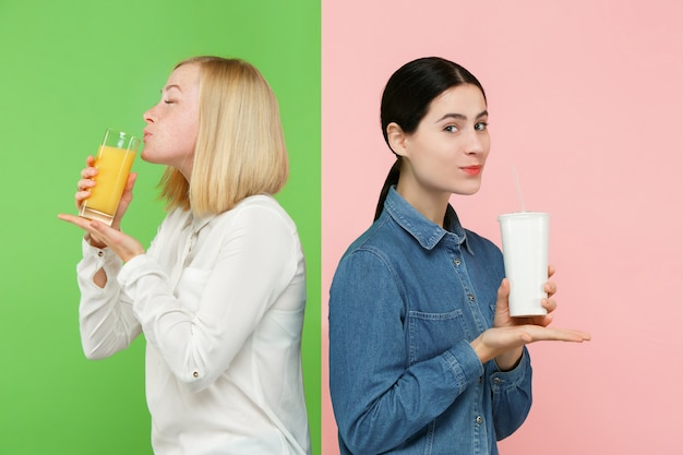 Рацион питания. концепция диеты. здоровая пища. красивые молодые женщины выбирают между фруктовым апельсиновым соком и безвкусным сладким газированным напитком