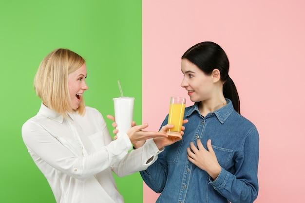 ダイエット。ダイエットの概念。健康食品。フルーツオレンジジュースと不健康な炭酸入りの甘い飲み物のどちらかを選ぶ美しい若い女性