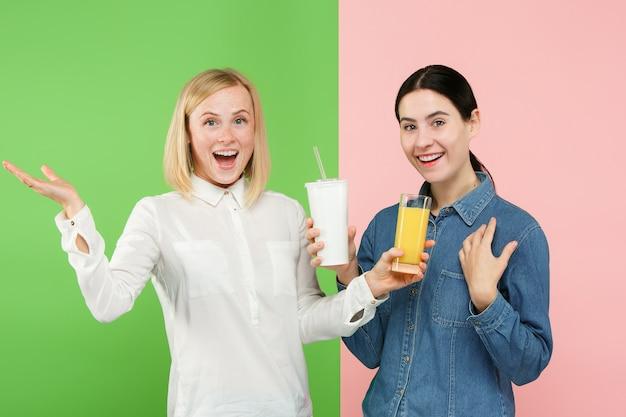 Диета. концепция диеты. здоровая пища. красивые молодые женщины выбирают между фруктовым апельсиновым соком и безвкусным сладким газированным напитком