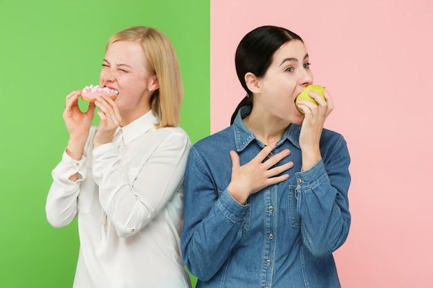 ダイエット。ダイエットのコンセプトです。健康食品。果物と不気味なケーキの間を選択する美しい若い女性