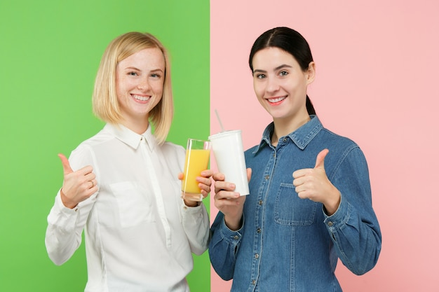 Diet. dieting concept. healthy food. beautiful young women choosing between fruit orange juice and unhelathy carbonated sweet drink