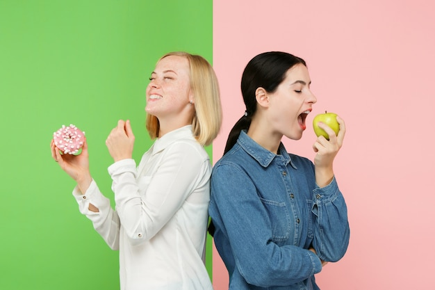 Diet. dieting concept. healthy food. beautiful young women choosing between fruits and unhelathy cake