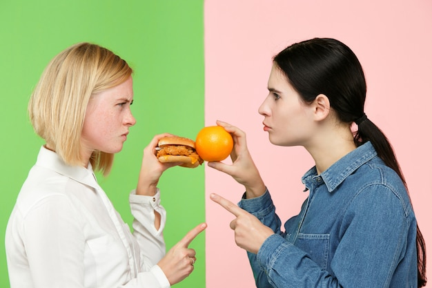 Dieta. concetto di dieta. cibo salutare. belle giovani donne che scelgono tra frutta e unhelathy fast food