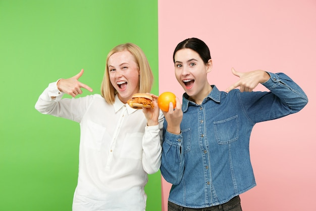 ダイエット。ダイエットのコンセプトです。健康に役立つ食品。スタジオで果物と不気味なファーストフードの間を選択する美しい若い女性。人間の感情と比較の概念