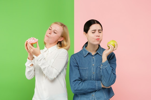 Diet. dieting concept. healthy useful food. beautiful young women choosing between fruits and unhelathy cake at studio. human emotions and comparison concepts