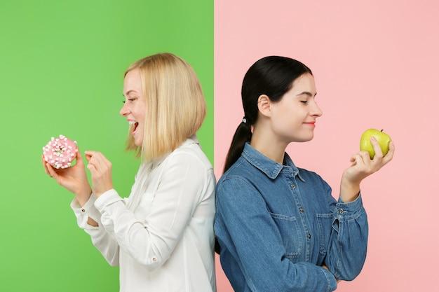 Dieta. concetto di dieta. cibo sano e utile. belle giovani donne che scelgono tra frutta e torta unhelathy in studio. emozioni umane e concetti di confronto
