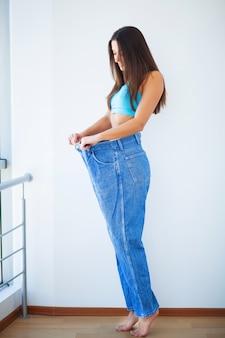 Рацион питания. концепция диеты. женщина в спортивной одежде измеряет свою талию