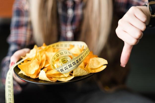 다이어트 대 패스트 푸드. 칩 스낵을 위해 엄지 손가락을 아래로 내리십시오. 건강한 라이프 스타일 선택