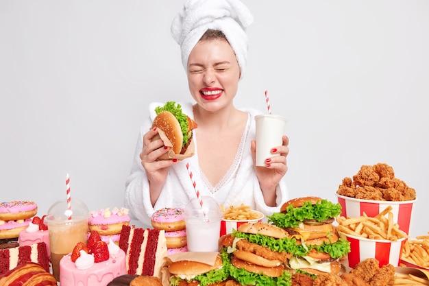다이어트 실패와 건강에 해로운 생활 방식 개념. 기뻐하는 젊은 여성이 햄버거와 탄산 음료를 들고 있다