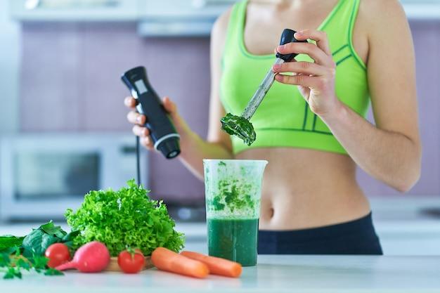 녹색 스무디 요리 손 믹서기를 사용하여 다이어트 맞는 여자.