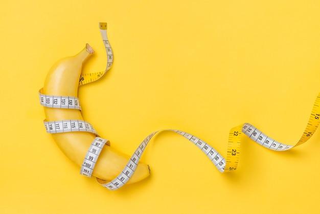 黄色い紙の背景に分離されたメジャーテープに包まれた黄色いバナナによって提示されたダイエット、フィットネス、健康の概念