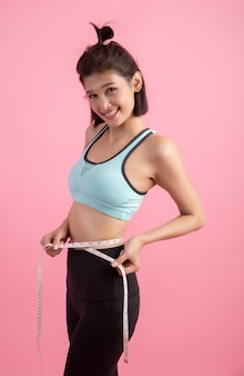 Diet fitness exercise sport sexy body happy smiling asian woman with measuring tape