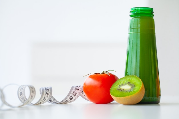 Diet. fitness and healthy food diet concept, green juice. fresh fruit, and glass water, measuring tape