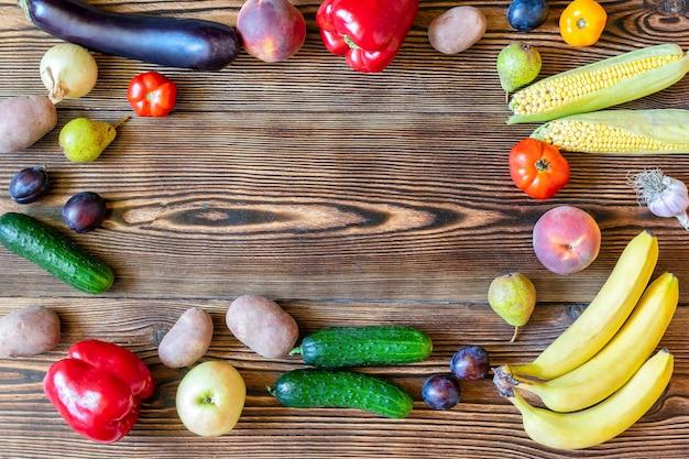木製の背景に新鮮な果物と野菜のサラダと夕食のためのダイエットフィットネスベジタリアンビーガンフード上面図コピースペースフレームフラットフラットレイ。秋の収穫のセット