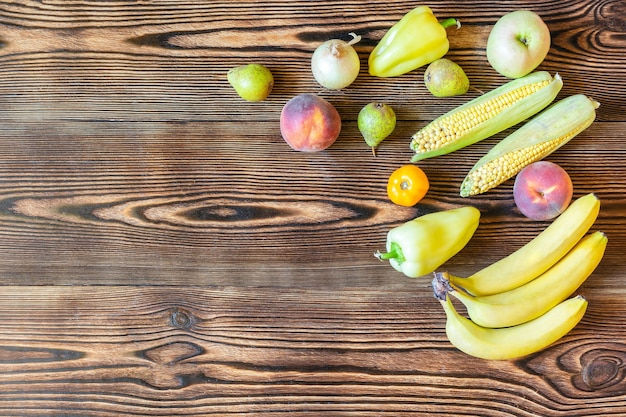 木製の背景に新鮮な黄色の果物と野菜を夕食にダイエットフィットネスベジタリアンビーガンフード上面図コピースペースフレームフラットフラットレイ。秋の収穫のセット