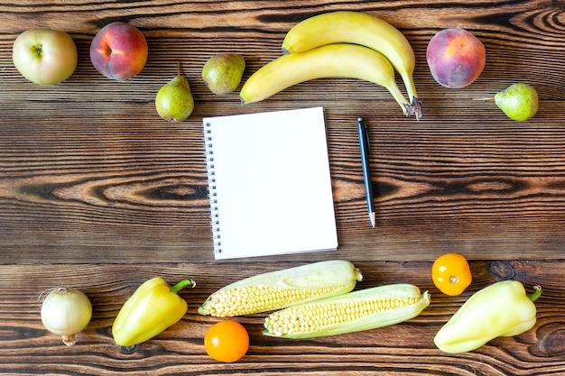 Диета, фитнес, вегетарианская веганская еда на ужин со свежими желтыми фруктами и овощами, план похудения с блокнотом и ручкой для заметок на деревянном фоне.