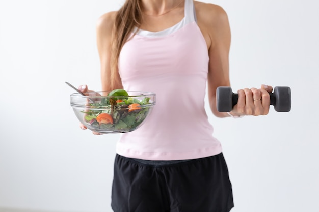 다이어트, 음식 및 피트니스 개념-흰색 배경 위에 여성 손에 건강 샐러드와 아령 닫습니다.