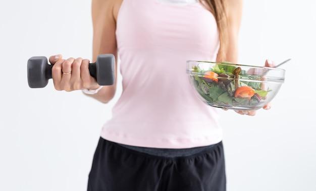 다이어트, 음식 및 피트니스 개념 - 흰색 배경 위에 여성의 손에 건강한 샐러드와 아령을 닫습니다.
