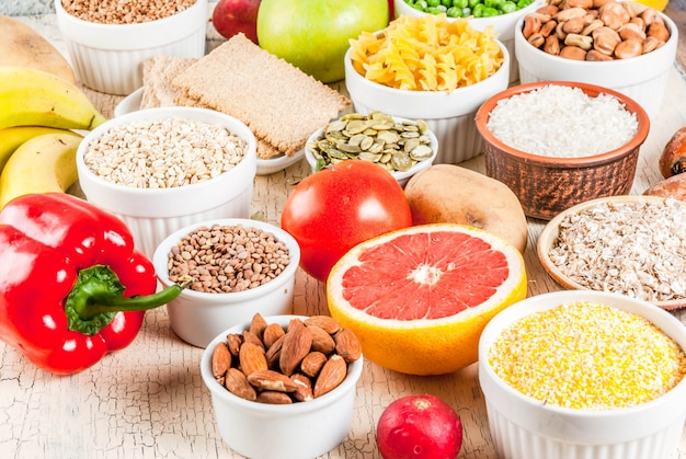 Diet food background concept, healthy carbohydrates (carbs) products - fruits, vegetables, cereals, nuts, beans, light concrete background