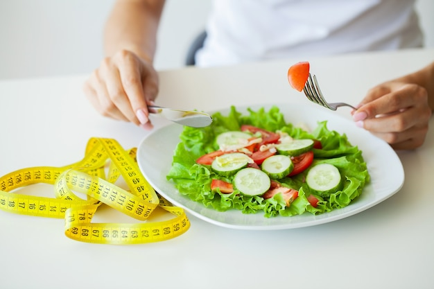 Diet food, closeup of fresh salad in a bowl and yellow measure tape.