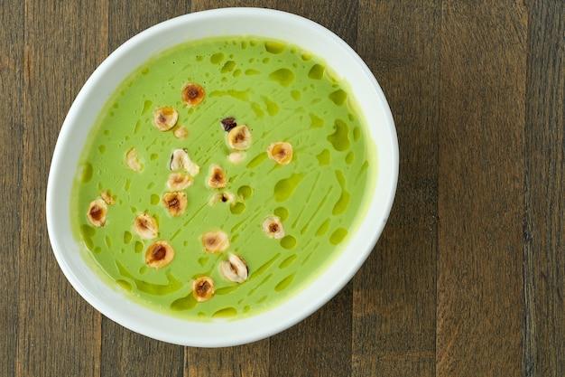 Диетическое питание - зеленый крем-суп из брокколи с фундуком и трюфельным маслом в белой миске на деревянной поверхности.