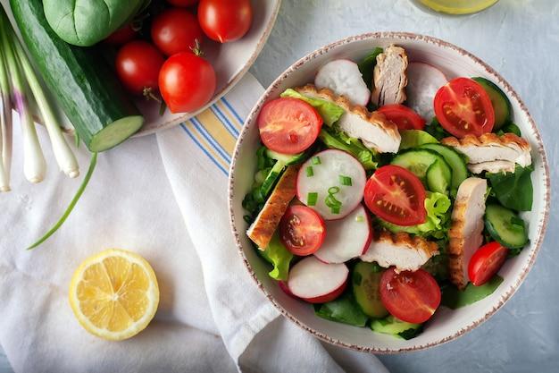 ダイエット食品。グリルした鶏胸肉とフィレとレタス、ほうれん草、きゅうり、トマトの新鮮野菜のサラダ。