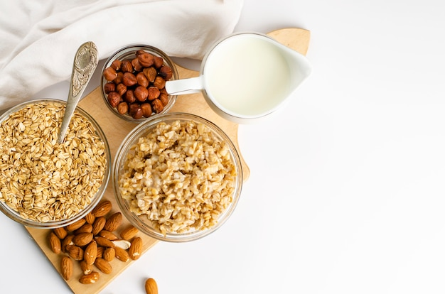 Diet food menu for breakfast with oats bowl with nuts and milk jar on wooden board