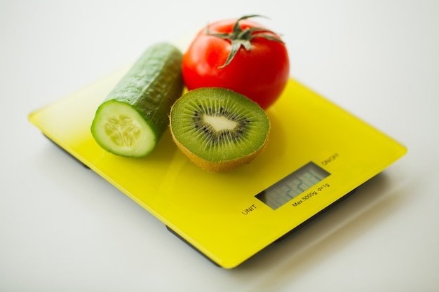 Diet, fruits and vegetables on weight scale