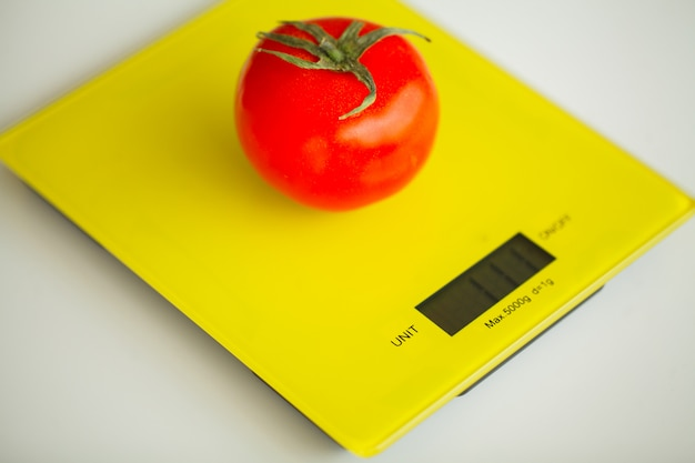 Diet, fruits and vegetables with measuring tape on weight scale