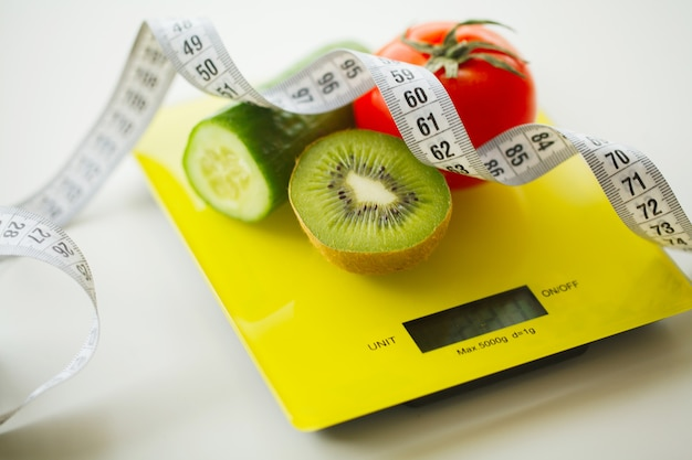 Diet. fruits and vegetables with measuring tape on weight scale